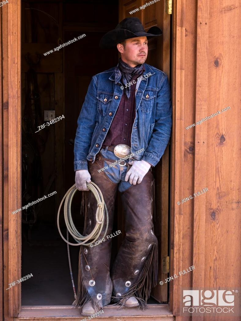 Imagen: A cowboy wrangler with his lariat on the Red Cliffs Ranch near Moab, Utah. He wears leather chaps to protect his legs from thorny brush while riding the range.