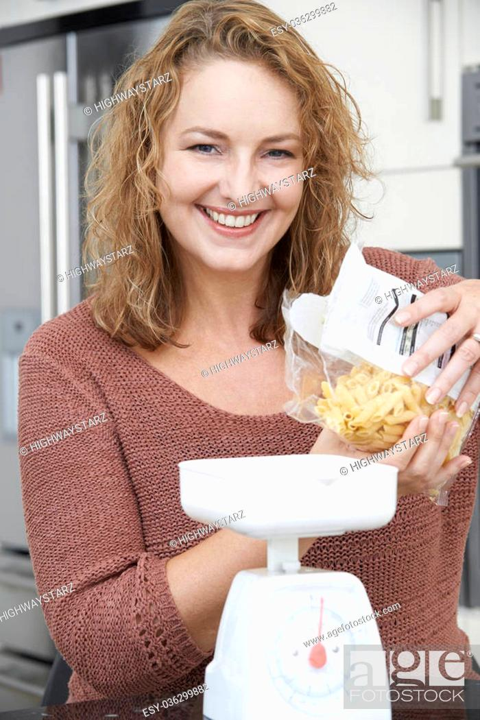 Stock Photo: Plus Size Woman On Diet Weighing Out Pasta For Meal.