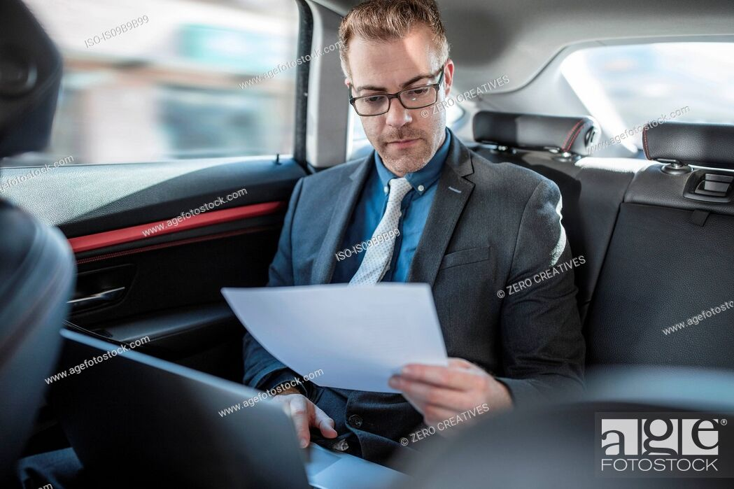 Stock Photo: Businessman sitting in back of car, using laptop, holding document.