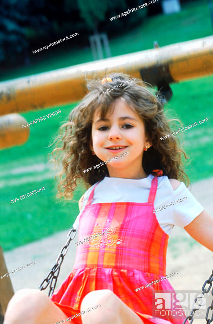 Stock Photo: Young girl sitting on a swing.