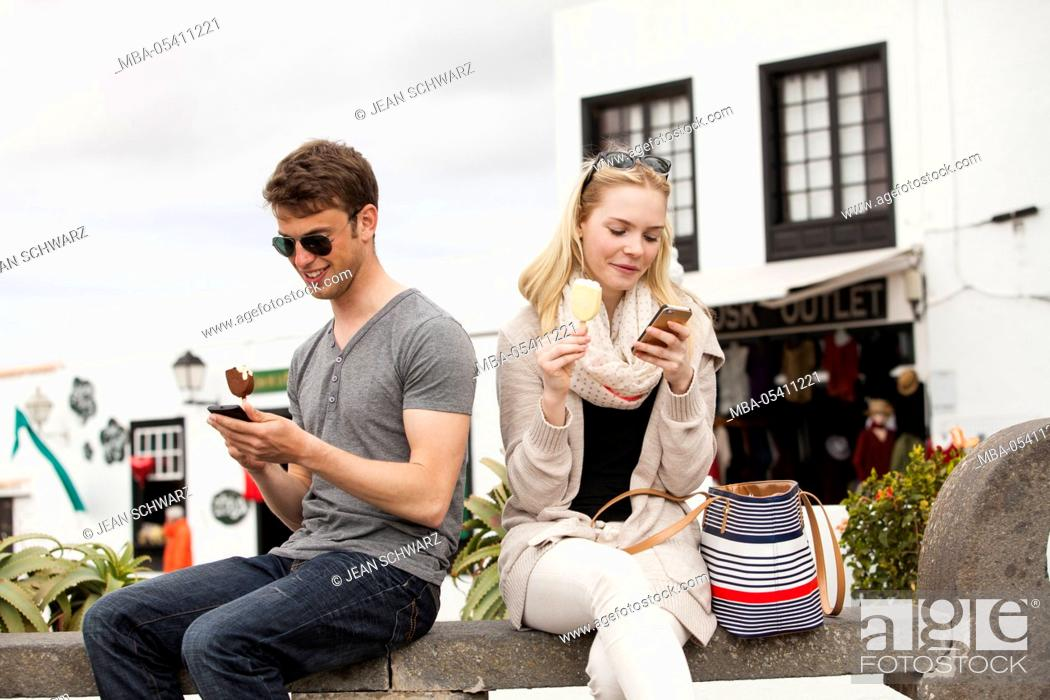 Imagen: young couple with mobile phones, eating ice cream,.