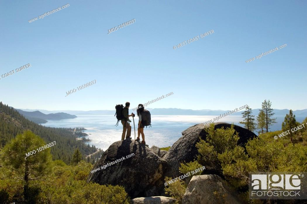 Stock Photo: Couple standing on rock at coast.