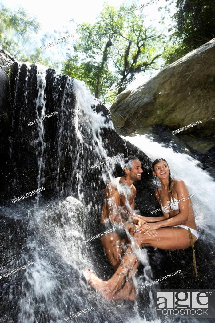 Stock Photo: Hispanic couple sitting under waterfall.