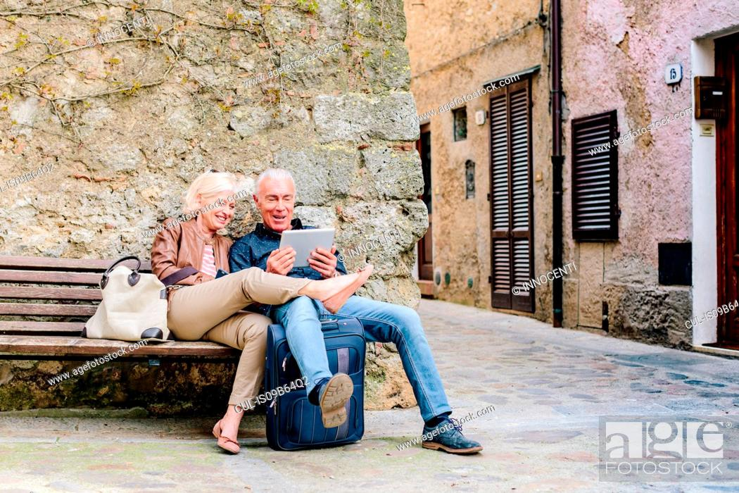 Stock Photo: Tourist couple sitting on bench looking at digital tablet in Siena, Tuscany, Italy.