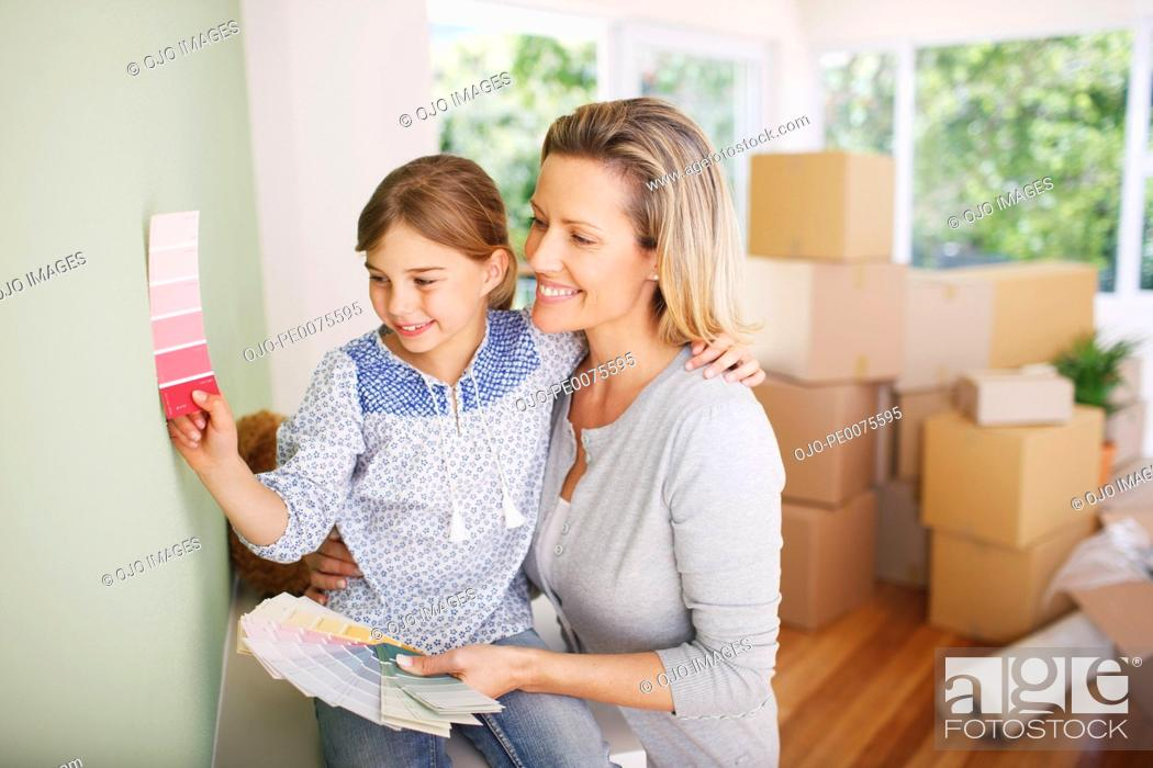 Stock Photo: Mother and daughter picking paint color for their new house.