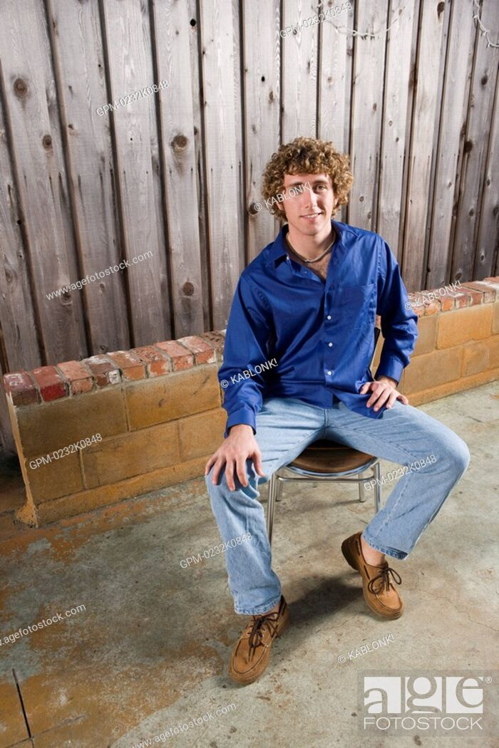 Imagen: Portrait of young man sitting in chair outside on patio, high angle view.