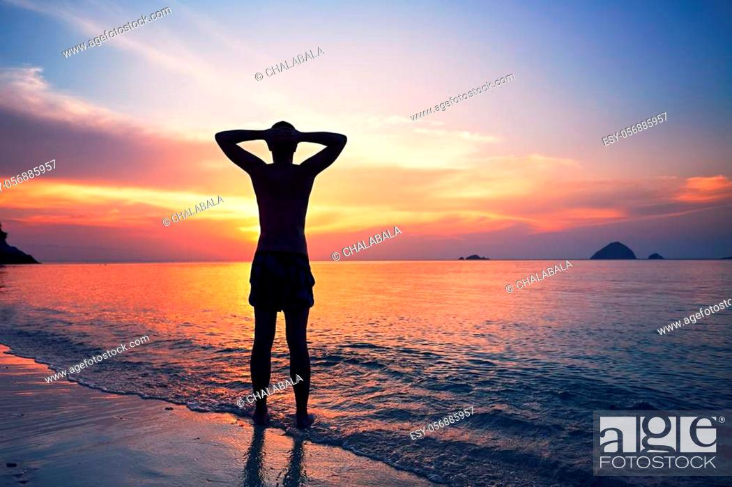 Stock Photo: Pensive young man standing in water of the tropical sea during beautiful sunset.