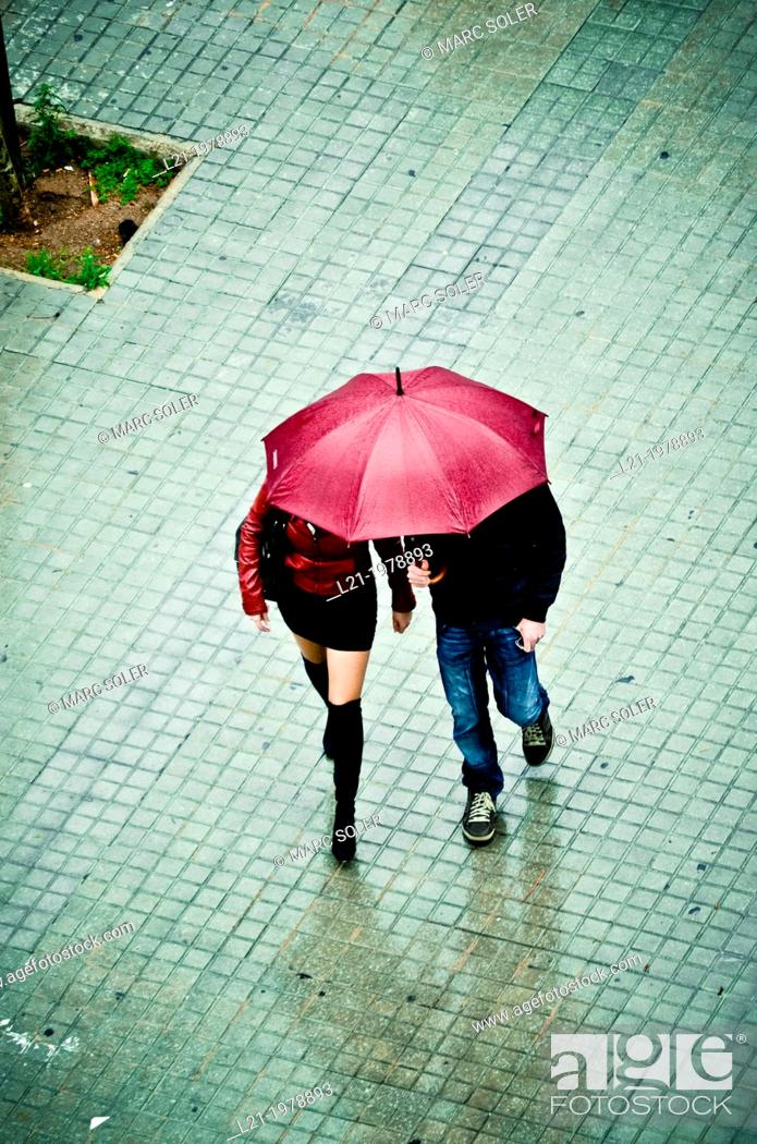 Stock Photo: Couple, man and woman, walk down the street under an umbrella. Viewpoint from above. Barcelona, Catalonia, Spain.