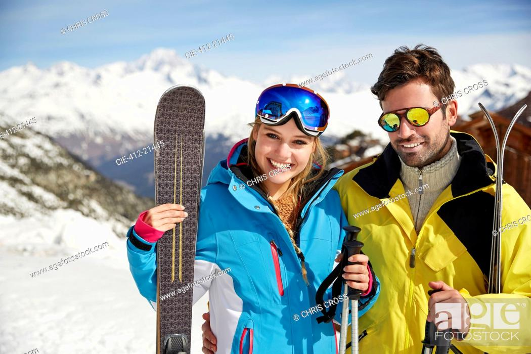 Photo de stock: Couple carrying skis on mountain top.