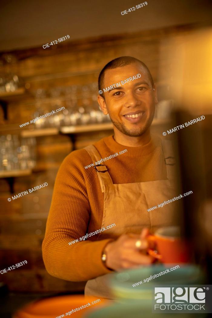 Stock Photo: Portrait smiling confident male barista preparing coffee in cafe.