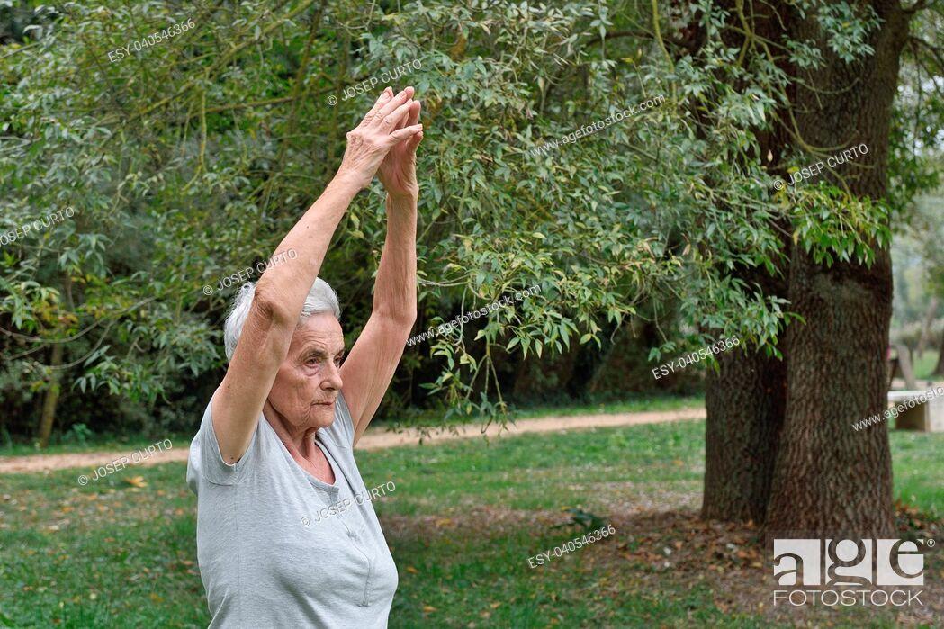 Stock Photo: elderly woman practicing yoga outdoors.