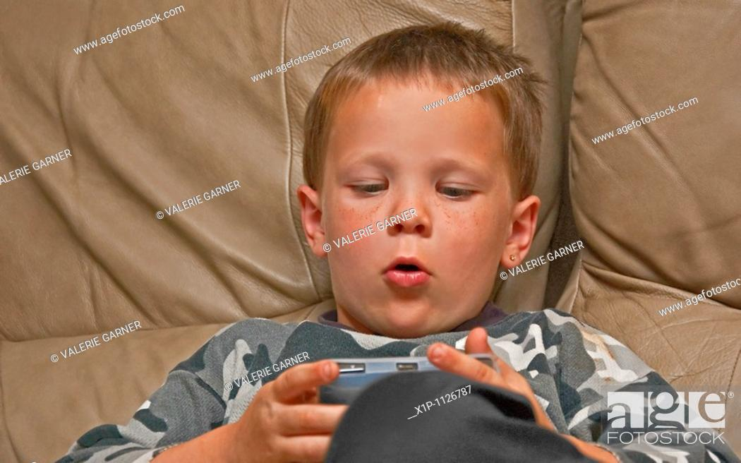 Stock Photo: This 5 year old Caucasian boy with freckles is concentrating as he's playing an electronic video game on a beige colored leather couch indoors.