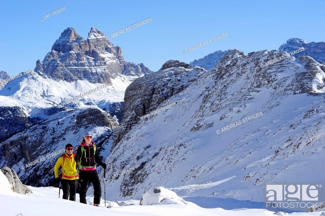 Stock Photo: Young woman and young man ascending with crosscountry skis to Corno d'Angolo, Tre Cime di Lavaredo in background, Corno d'Angolo, Cortina, Veneto, Dolomites.