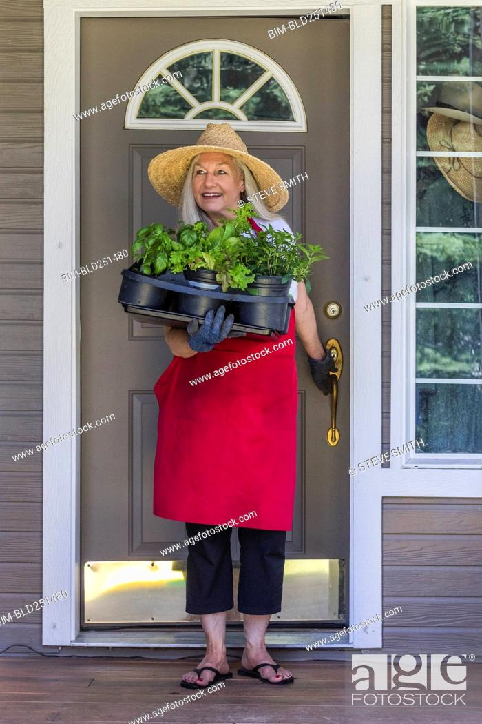 Stock Photo: Caucasian woman holding potted plants in doorway.