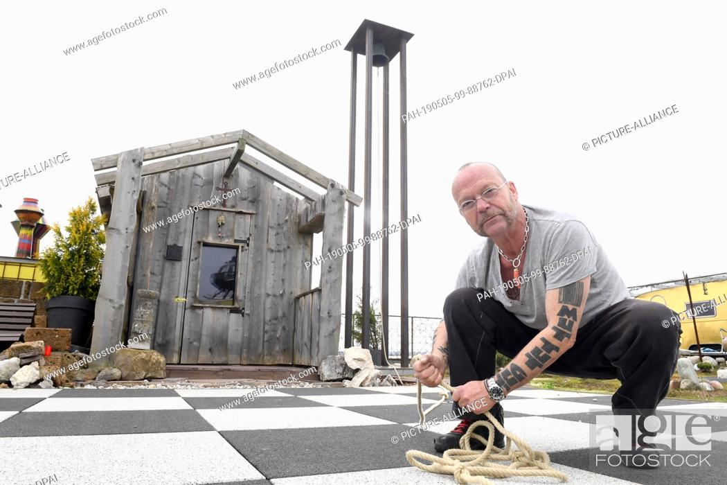 Photo de stock: 27 March 2019, Bavaria, Munich: Wolfgang Flatz, Austrian action artist, stage designer, musician and composer, sits on the roof of the Kistlerhof in front of a.