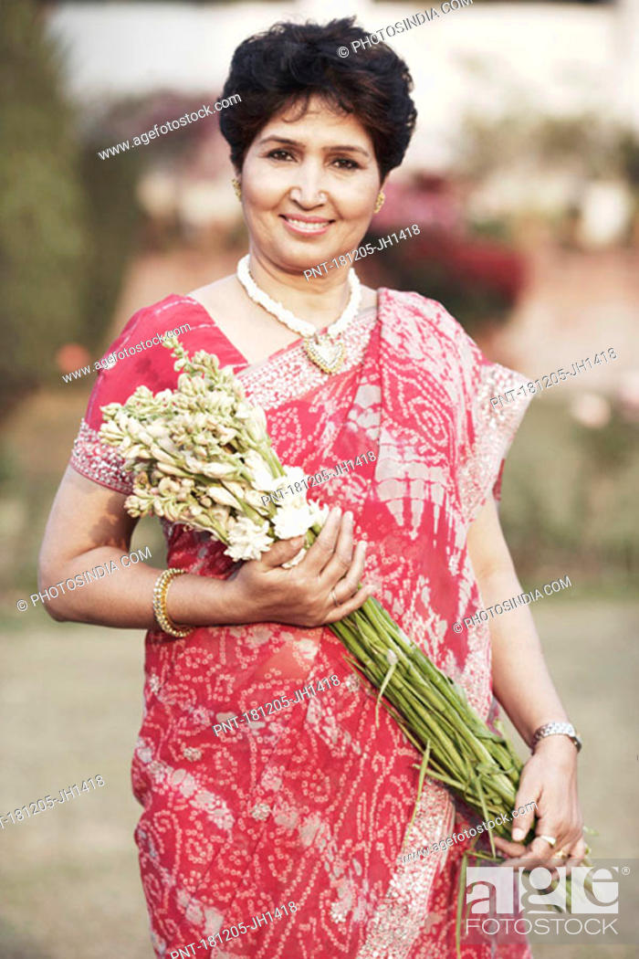 Stock Photo: Portrait of a mature woman holding a bunch of flowers.