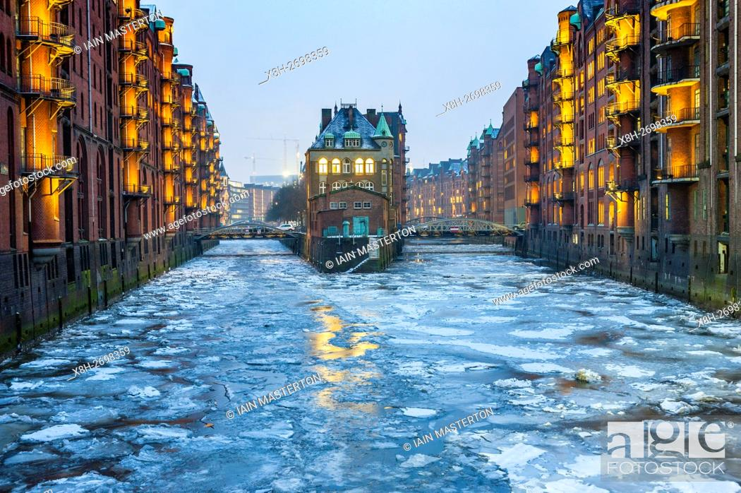 Stock Photo: View of historic red brick warehouses with frozen canals in winter at Speicherstadt beside canals in Hamburg Germany.