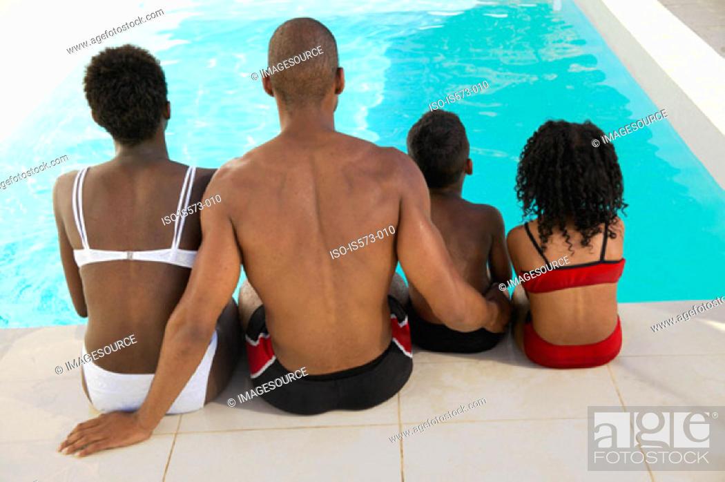 Stock Photo: Family sitting near pool.