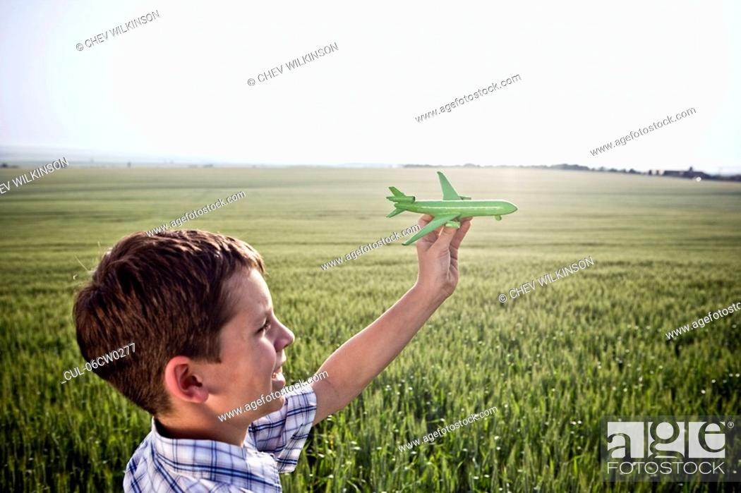 Stock Photo: Boy playing with toy plane.