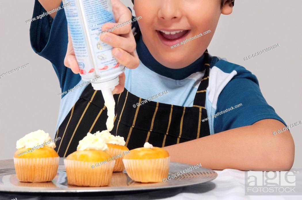 Stock Photo: Close-up of a boy putting whipped cream on cupcakes.