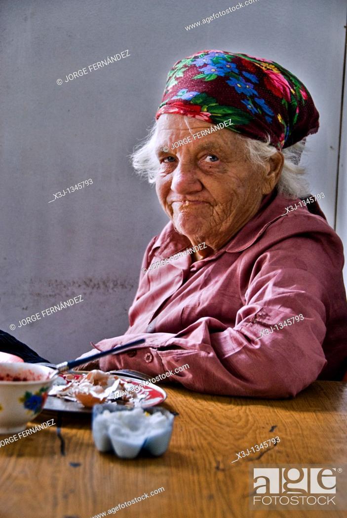 Imagen: Old, poor woman eating in a food stall  Bishkek, Kyrgyzstan.