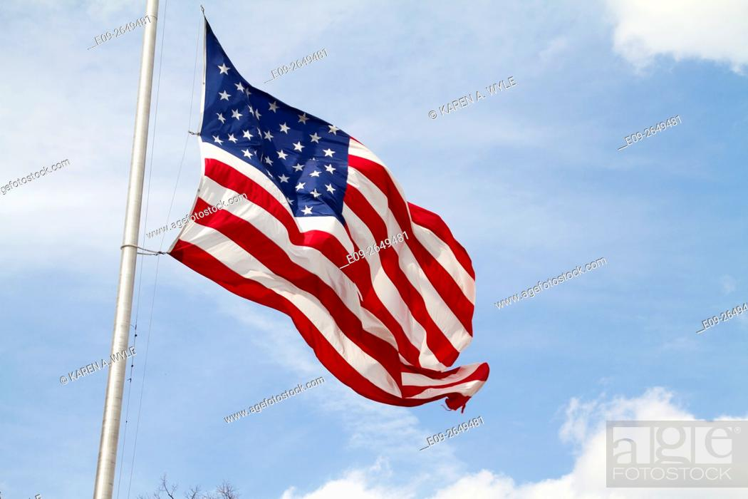 Stock Photo: American flag rippling in the wind against partly blue, partly cloudy sky, Bloomington, Indiana.