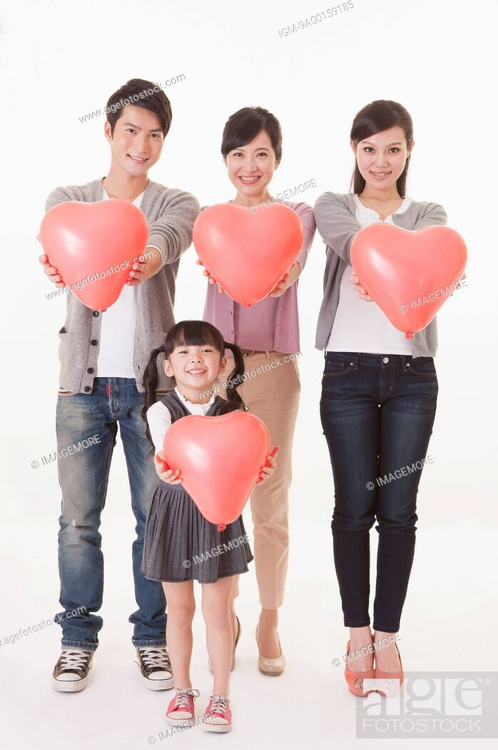 Imagen: Three generation family standing and holding balloon with smile.