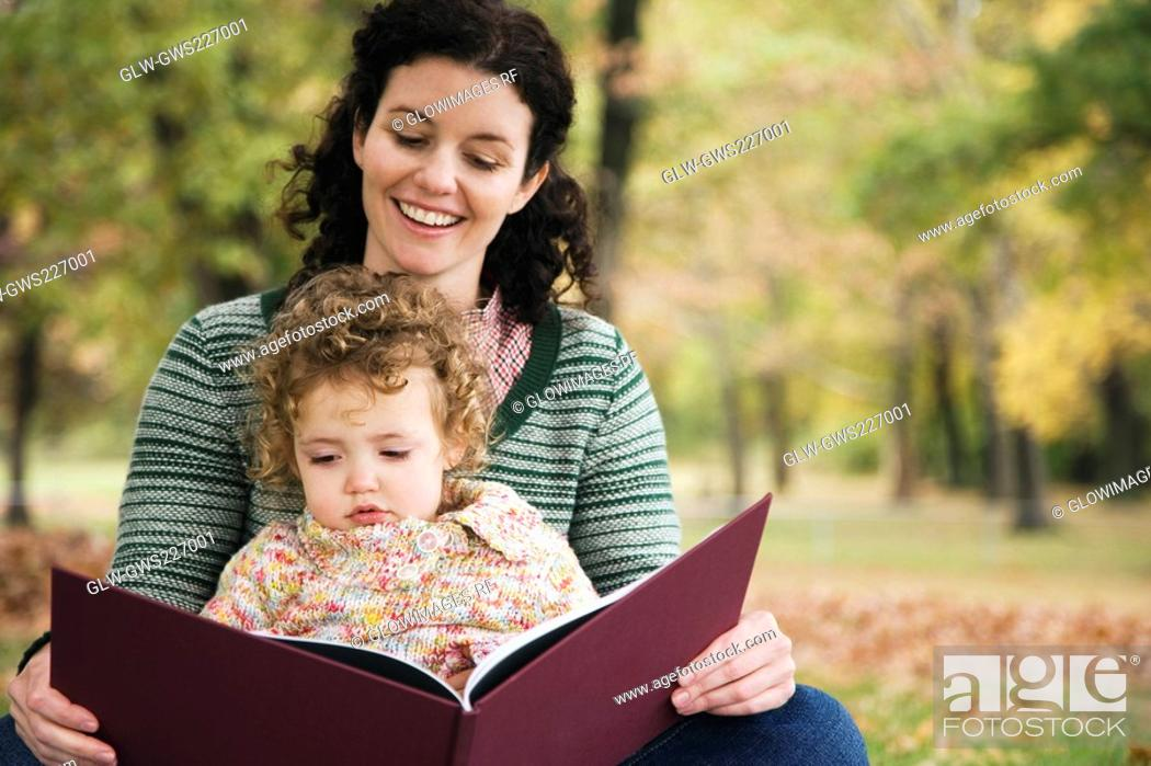 Stock Photo: Mid adult woman and her daughter looking at a picture book.