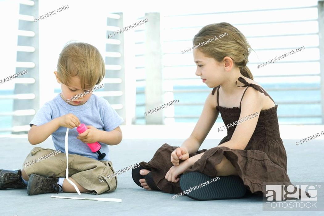 Stock Photo: Little boy sitting on the ground inflating balloon with air pump, older sister watching.