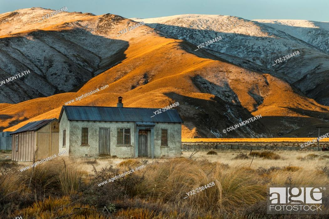 Imagen: 1939 farm cottage (still in use as tea room for shearers), early winter snowfall on Hawkdun Range, St Bathans, Central Otago.
