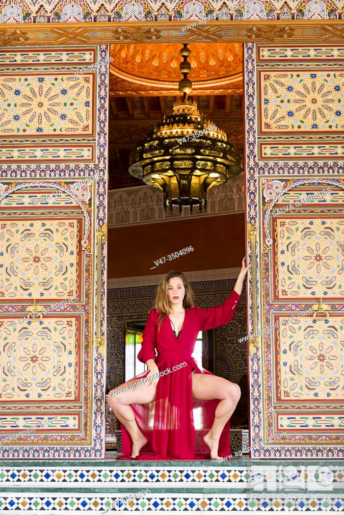 Stock Photo: Woman in a red dress leaning against the mosaic doors of the halls of an Arab palace.