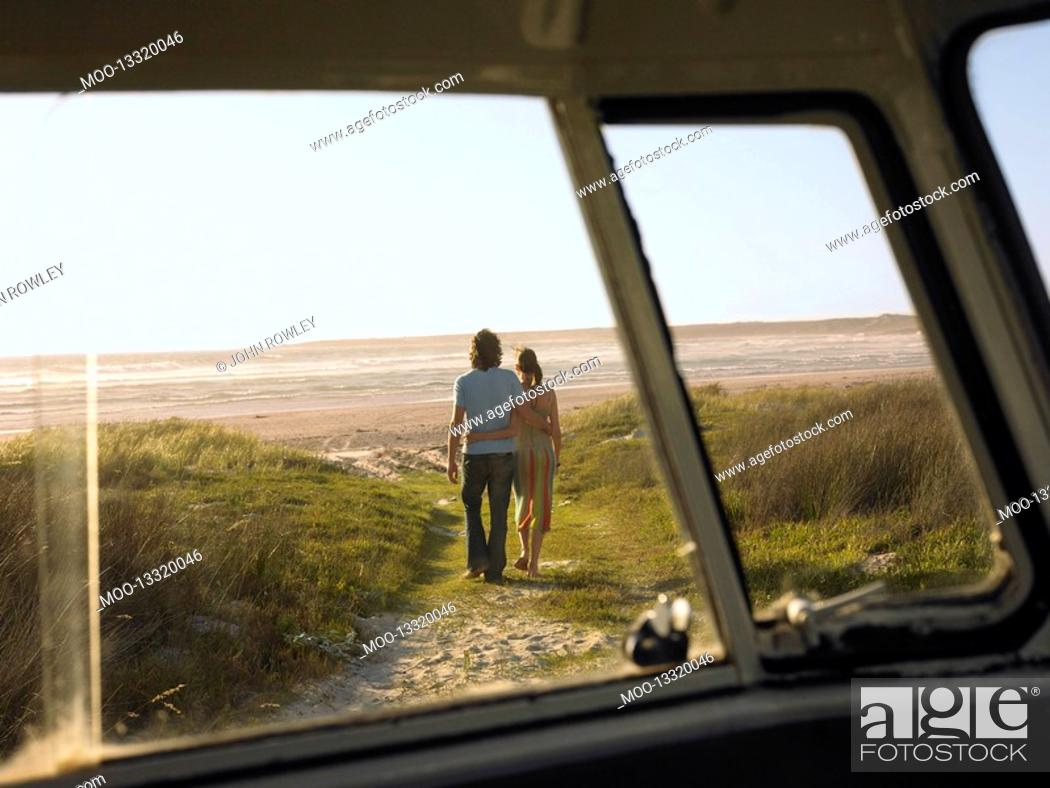 Stock Photo: Couple walking away from camper van towards beach view through camper van window.