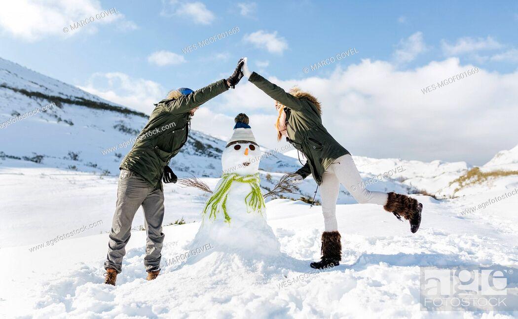 Stock Photo: Spain, Asturias, couple with a snowman.