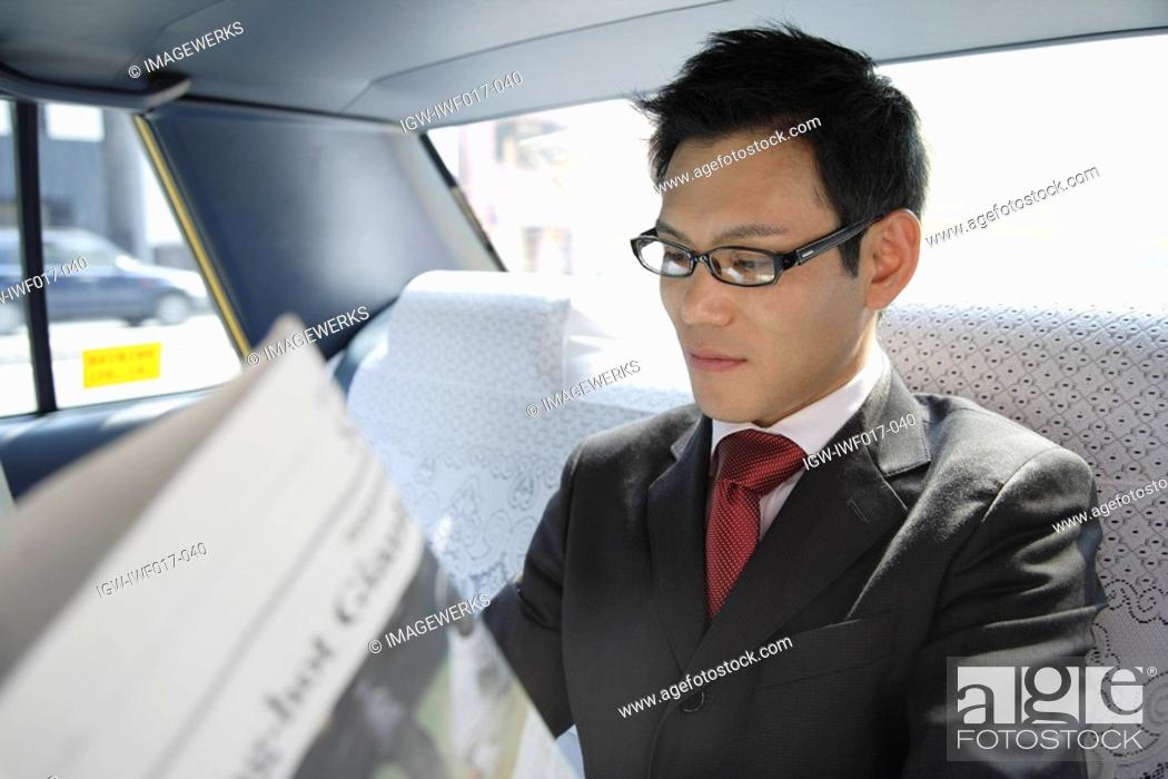 Stock Photo: Businessman reading a newspaper in a car, portrait.