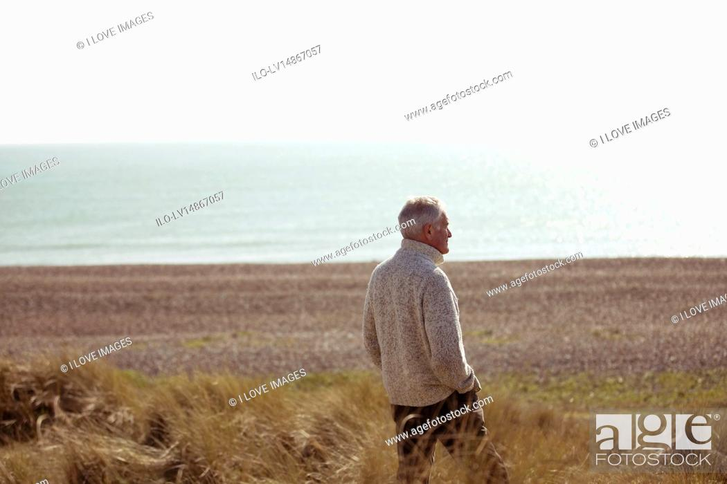 Stock Photo: A senior man standing amongst the sand dunes, looking out to sea.