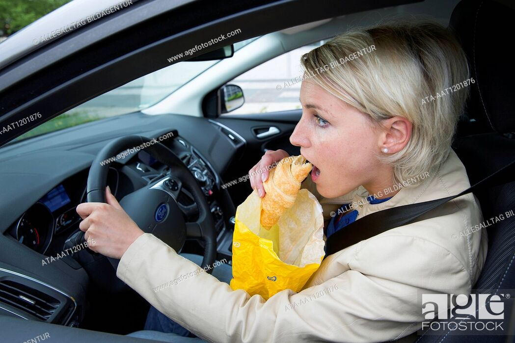 Stock Photo: Female car driver eats a croissant.