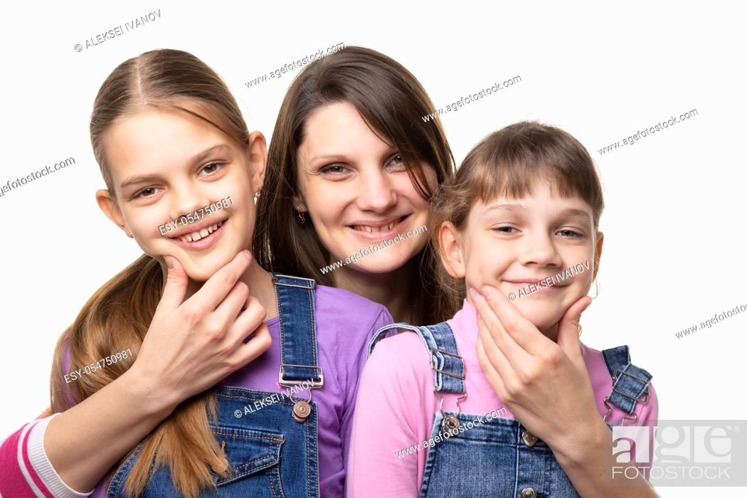 Stock Photo: Mom cheerfully holds the children by the chin and looks in the frame.