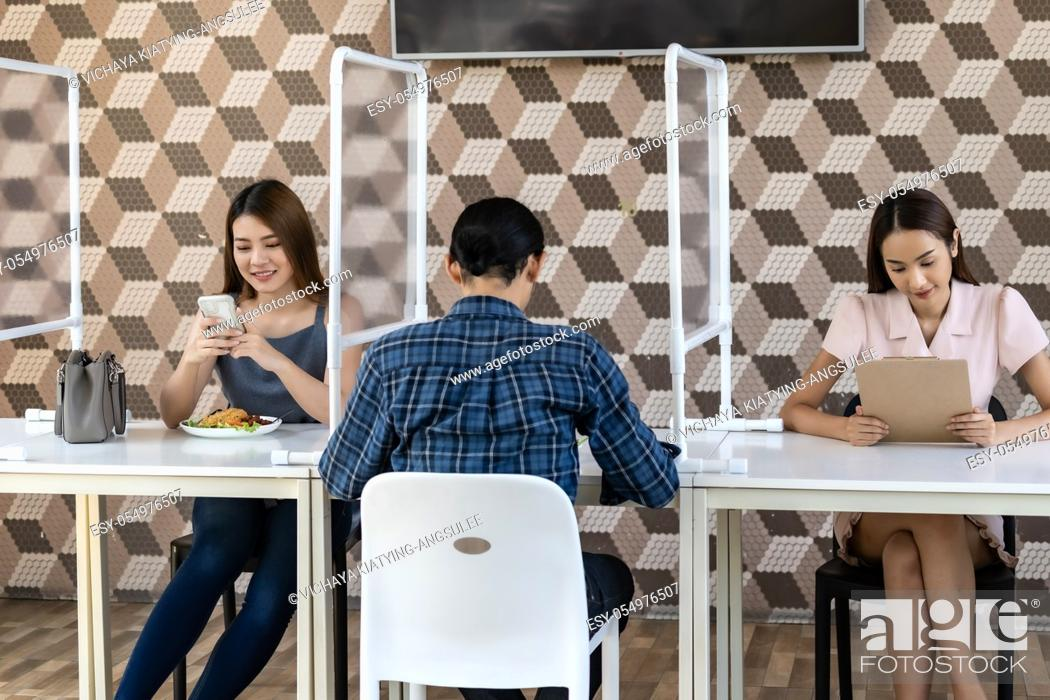 Stock Photo: Restaurant customers have a seat with table shield partition for social distancing to reduce infection of coronavirus covid-19 pandemic.