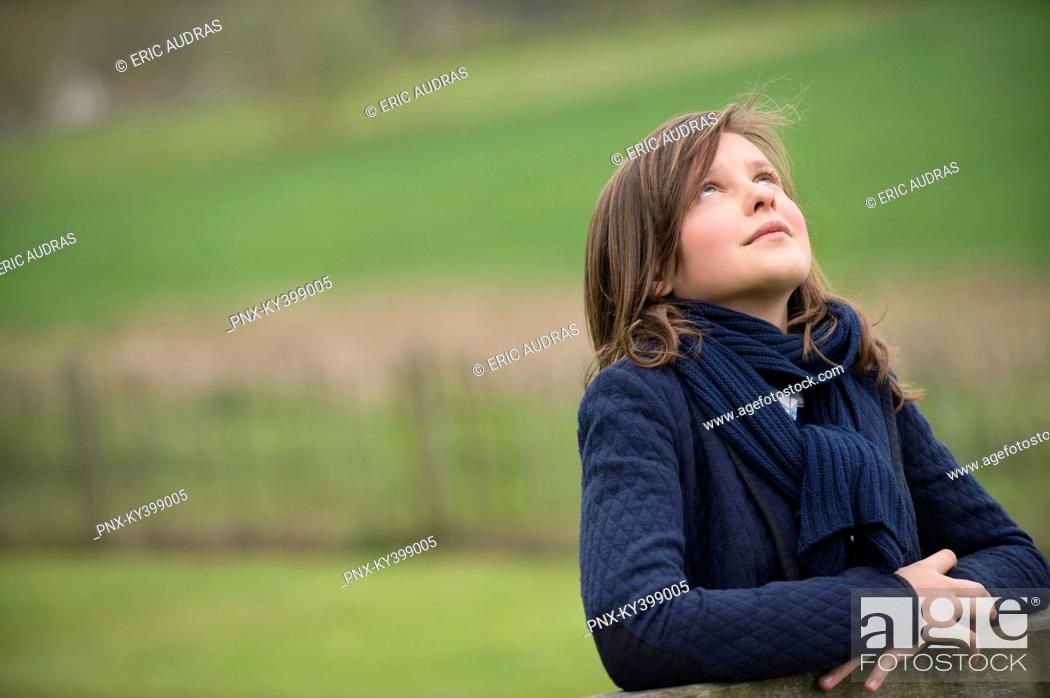 Stock Photo: Girl looking up in a farm.