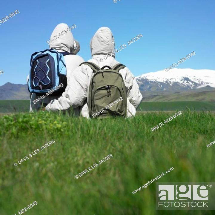 Stock Photo: Rear view of couple wearing winter jackets looking at snow-capped mountains.