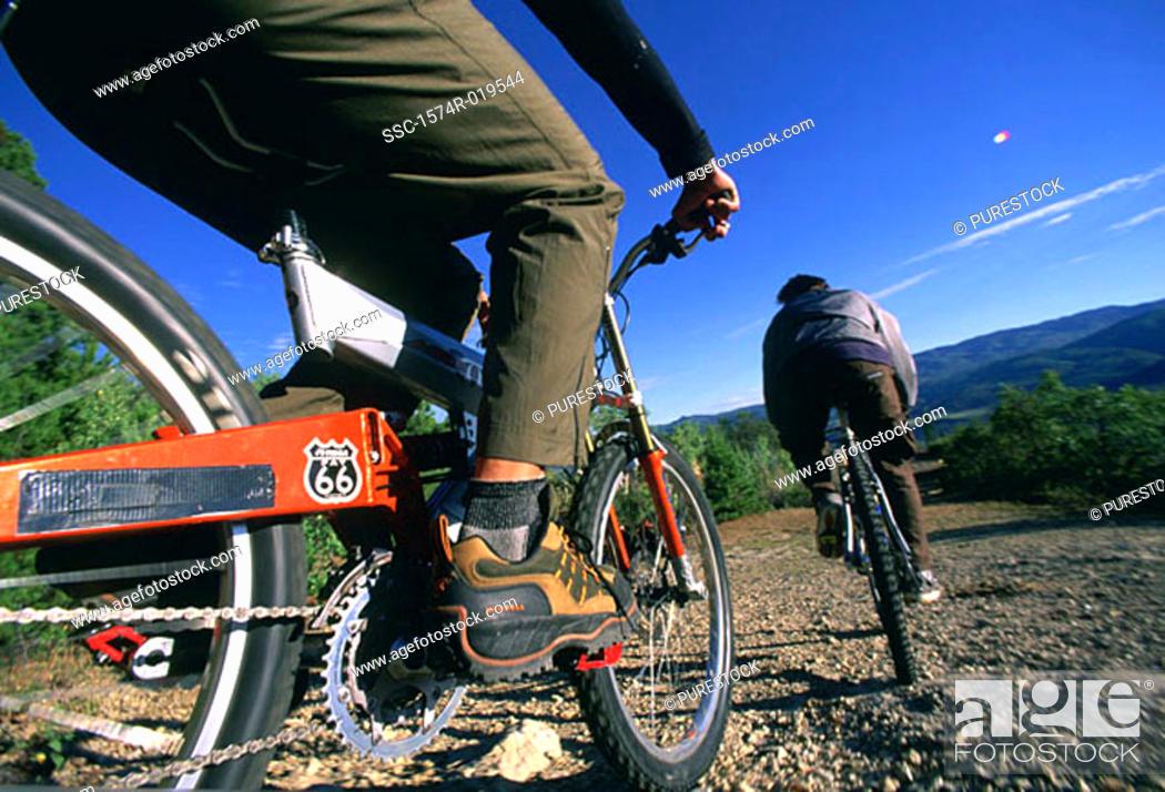 Stock Photo: Two people mountain biking.
