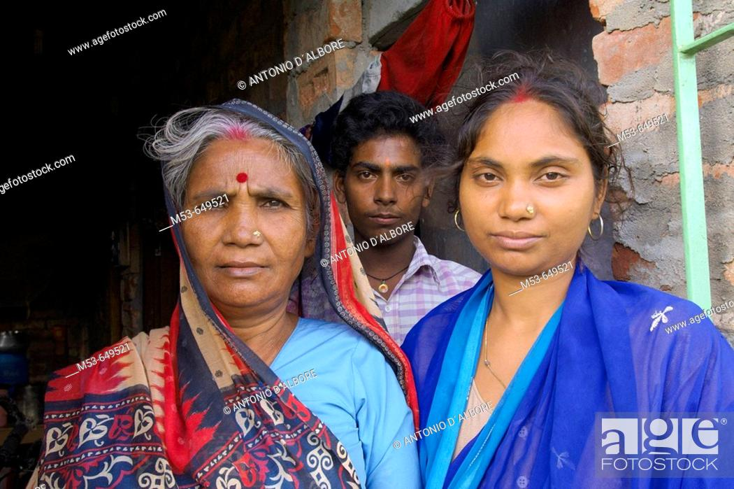 Stock Photo: a mother, doughter and son on the doorstep of their home in dhapa district. kolkata. west bengal. india. asia.