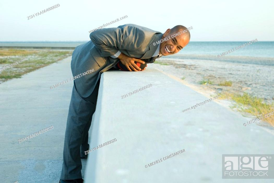 Stock Photo: Businessman leaning over low wall at the beach, smiling at camera.