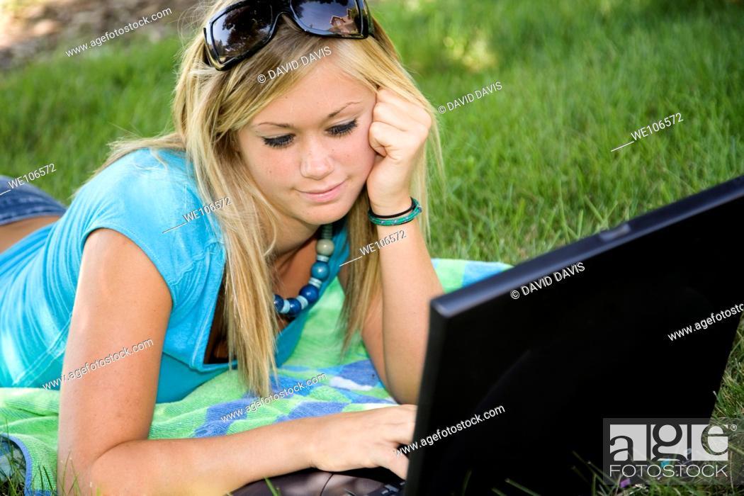 Stock Photo: Teenage girl working on laptop computer outdoors.