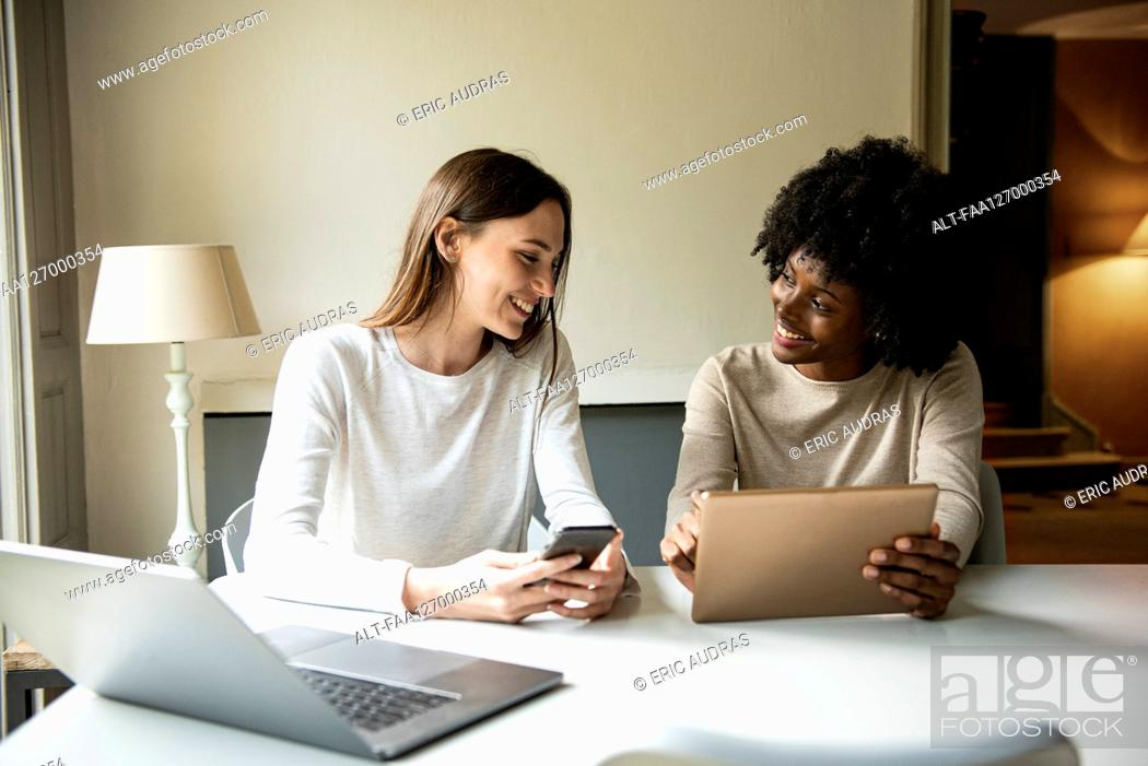 Photo de stock: Smiling young women using digital tablet and smart phone at home.
