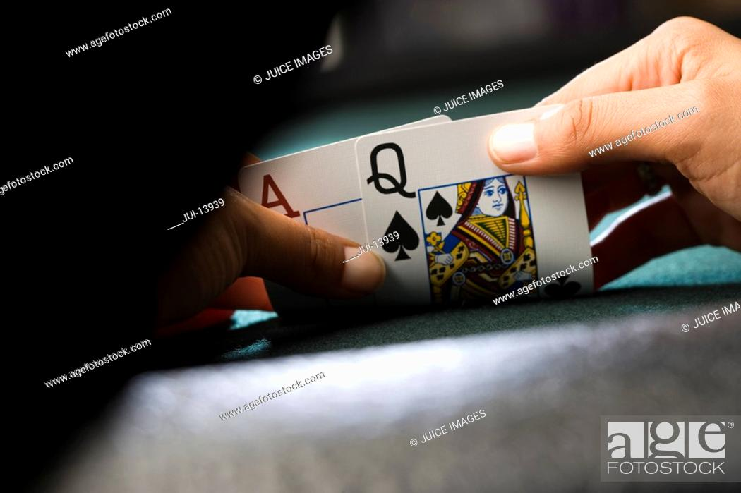 Stock Photo: Woman looking at playing cards at poker table, close-up of hands.