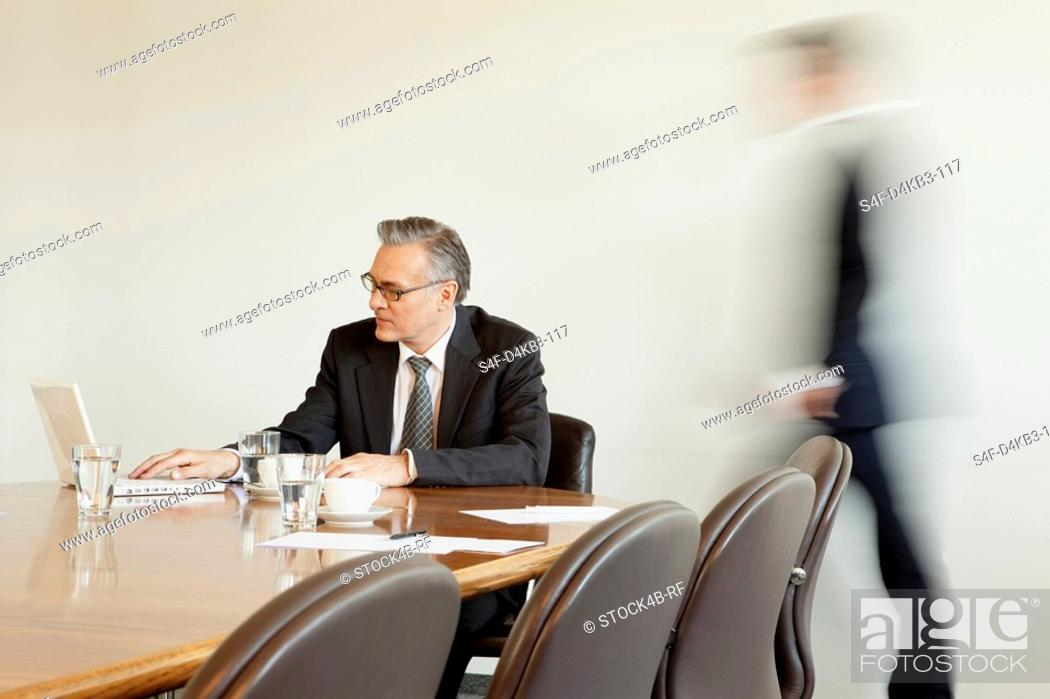 Stock Photo: Businessman in conference room with person in background passing by, Munich, Bavaria, Germany.