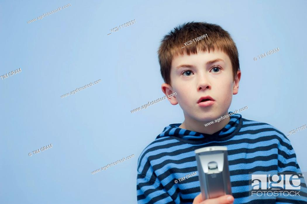 Stock Photo: A  picture of a ten year old boy with the Tv remote control indoors in the Uk.