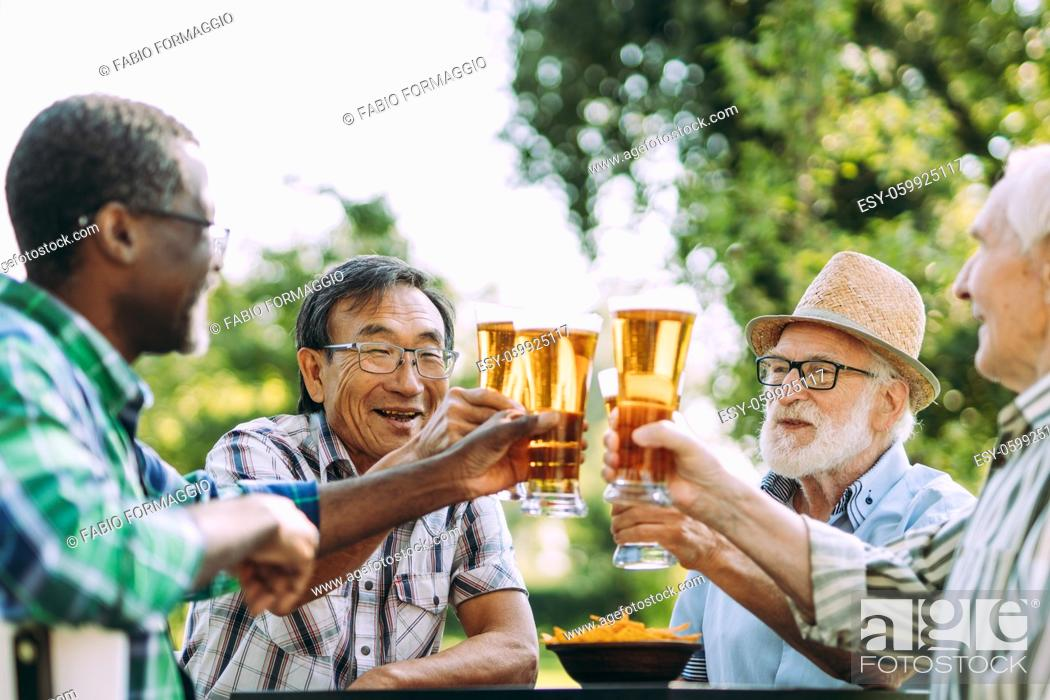 Stock Photo: group of senior friends drinking a beer at the park. Lifestyle concepts about seniority and third age.