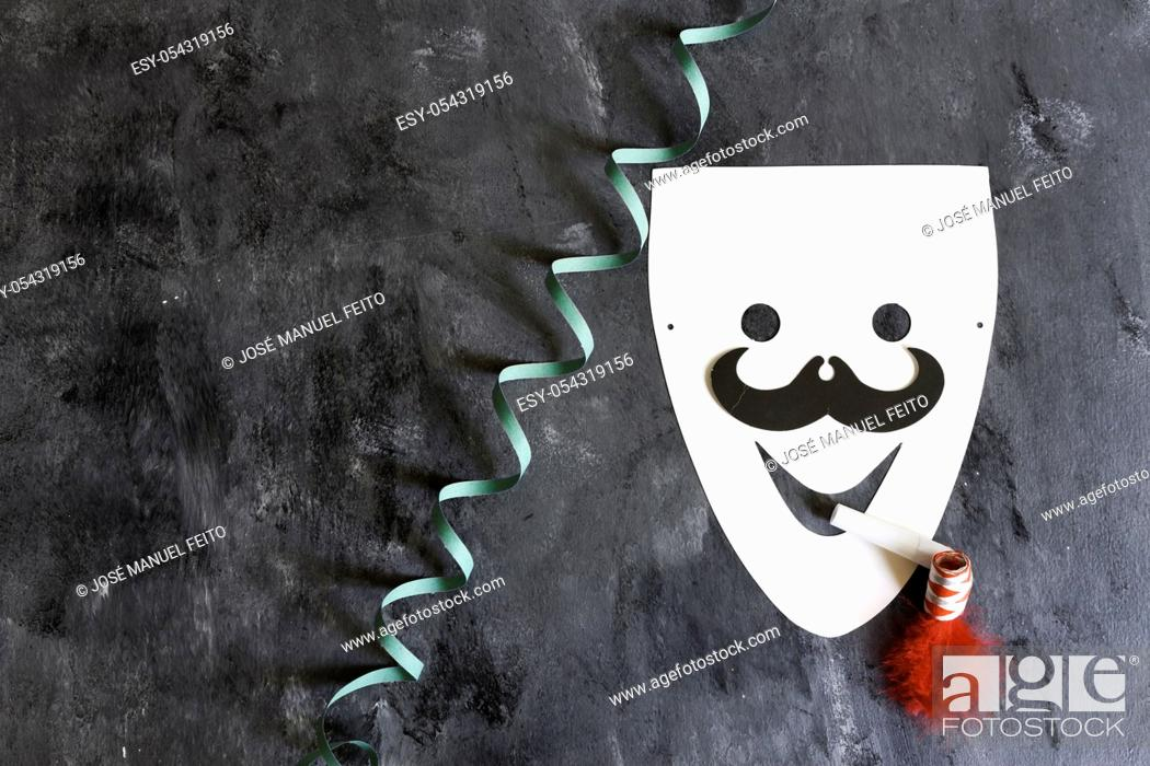 Stock Photo: paperboard mask with serpentine and matasuegras on dark background.